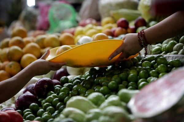 A woman buys oranges at a market stall in Mexico City, Mexico February 22, 2019. REUTERS/Daniel Becerril/File Photo GLOBAL BUSINESS WEEK AHEAD