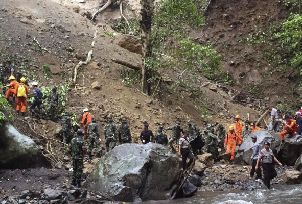 Indonesian soldier and rescue team search for earthquake victims in Bayan, North Lombok, Indonesia, Monday, March 18, 2019. Officials say an earthquake has triggered a landslide that hit a popular waterfall on Indonesia's Lombok island.(AP Photo/Bimbo)
