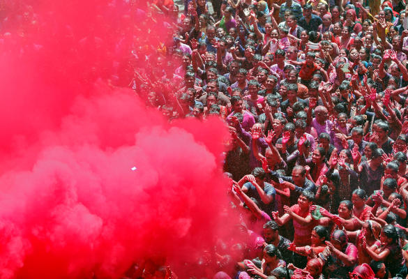 Hindu devotees pray as they are sprayed with colours by a priest on a temple premises during Holi celebrations in Ahmedabad, India, March 20, 2019. REUTERS/Amit Dave