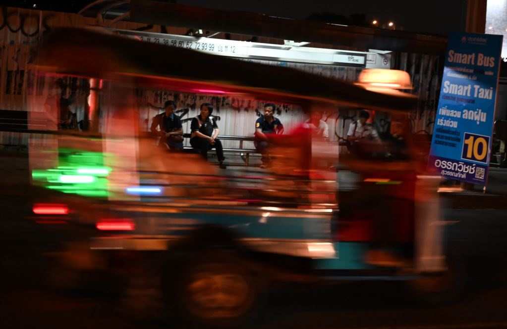 A tuktuk drives past people waiting for buses at a bus stop in Bangkok, Thailand. (AFP)