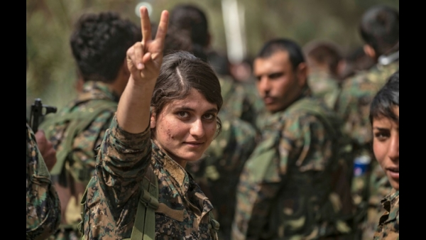 A female fighter of the US-backed Kurdish-led Syrian Democratic Forces (SDF) flashes the victory gesture while celebrating the elimination of ISIS group near the Omar oil field in the eastern Syrian Deir Ezzor province  AFP / Delil souleiman