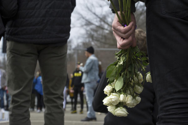 A person holds roses during a vigil for Antwon Rose II at the basketball court in the Hawkins Village housing complex, where Rose used to play in Rankin neighborhood, southeast of Pittsburgh on Sunday, March 24, 2019. (Pittsburgh Post-Gazette via AP)