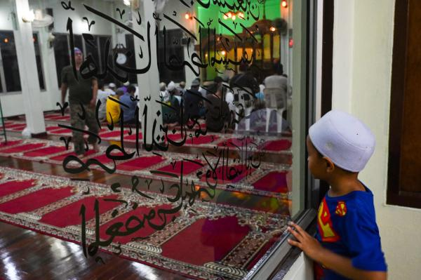A Muslim boy looks at devotees offering special Taraweeh prayers in Darul Falah mosque during the holy month of Ramadan in Bangkok on May 21, 2019. (Photo by Romeo GACAD / AFP)