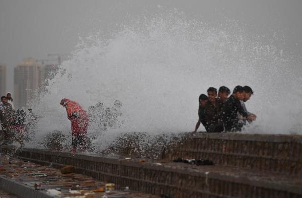 In this picture taken on June 14, 2019, people enjoy getting splashed by breaking waves during high tide at the sea front of the Arabian Sea in Karachi. (AFP)