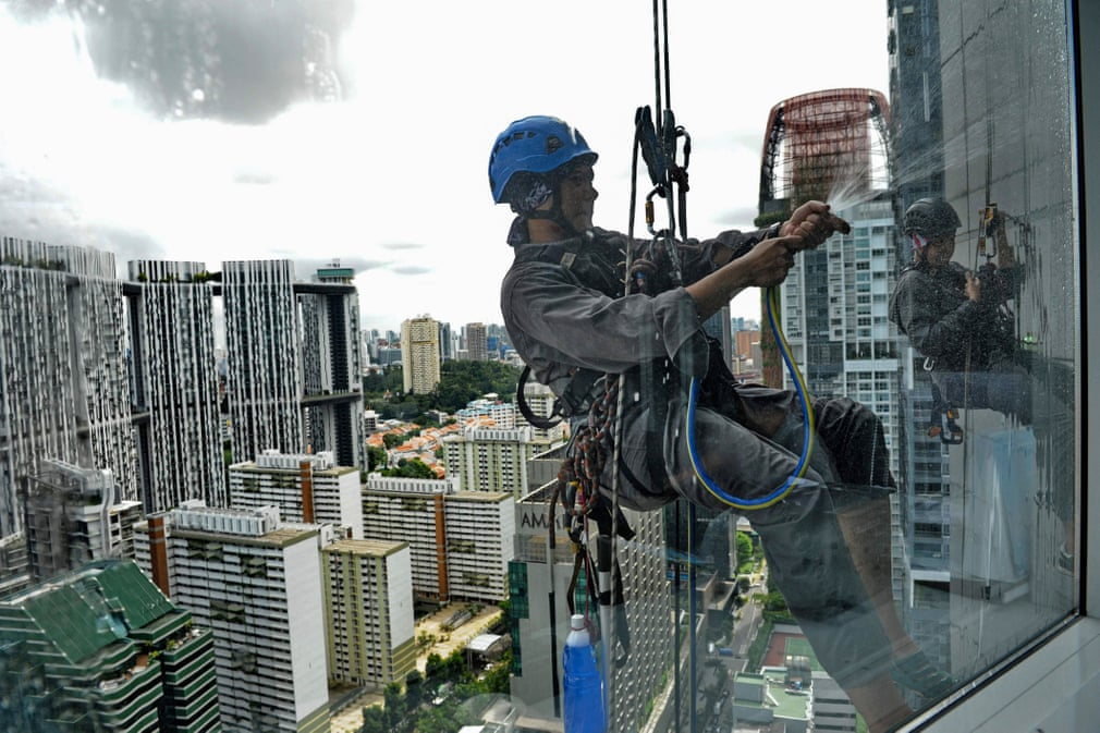 Workers clean the windows of a high-rise building in Singapore. (Getty Images)