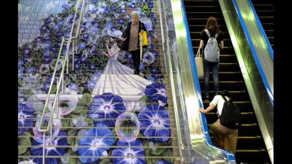 A commuter walks down stairs adorned with artwork of a girl surrounded by morning glories at an entrance of the station in Kumagaya, Saitama, Japan  AFP / Kazuhiro NOGI