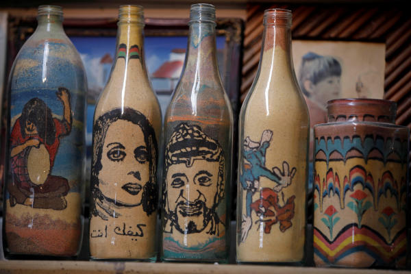 Colored sand artwork bearing the likeness of late Palestinian leader Yasser Arafat is displayed in a souvenir shop owned by Palestinian craftsman Mohammed Al-Awawda, in Hebron, in the Israeli-occupied West Bank. (Reuters)