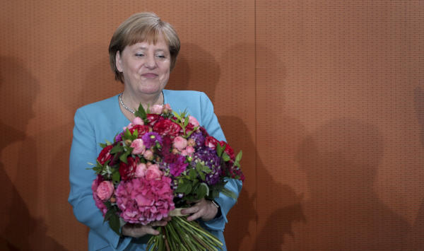 German Chancellor Angela Merkel holds a bunch of flowers that she received as a birthday present prior to the weekly cabinet meeting at the Chancellery in Berlin, Germany, Wednesday, July 17, 2019. (AP)
