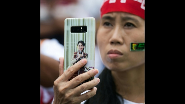 A woman holding a mobile phone with an image of Myanmar's State Counsellor Aung San Suu Kyi takes a video during a protest in support of amendments to the 2008 Myanmar Constitution in Yangon  AFP / Sai Aung MAIN
