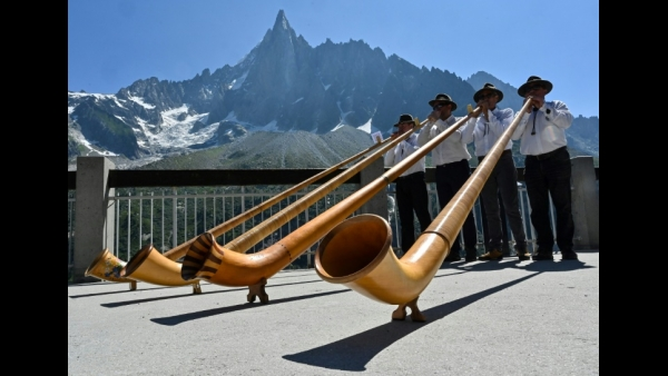 People play alphorns in front of the Drus peak (3754 m), on the