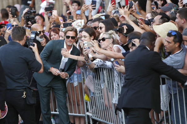 Brad Pitt (2-L) poses with fans as he arrives for the premiere of 'Once Upon a Time in Hollywood' at the TCL Chinese Theater IMAX in Hollywood, Los Angeles, California, 22 July 2019. (EPA)