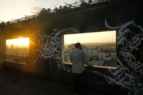 A Palestinian man gazes at Gaza City from a rooftop ornated with Arabic calligraphy on August 19, 2019. (AFP)