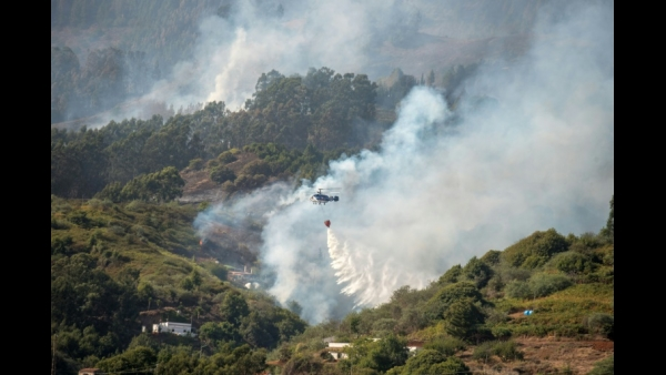 A helicopter drops water over a forest fire raging in the Moya mountains in Spain on the island of Gran Canaria  AFP / DESIREE MARTIN
