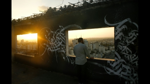 A Palestinian man gazes at Gaza City from a rooftop ornated with Arabic calligraphy  AFP / MOHAMMED ABED