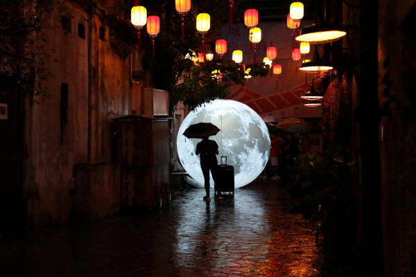 A tourist stands in front of a moon installation ahead of celebrations for the Mid-Autumn Festival at China Town in Kuala Lumpur, Malaysia, August 24, 2019. Picture taken August 24, 2019. REUTERS/Lim Huey Teng