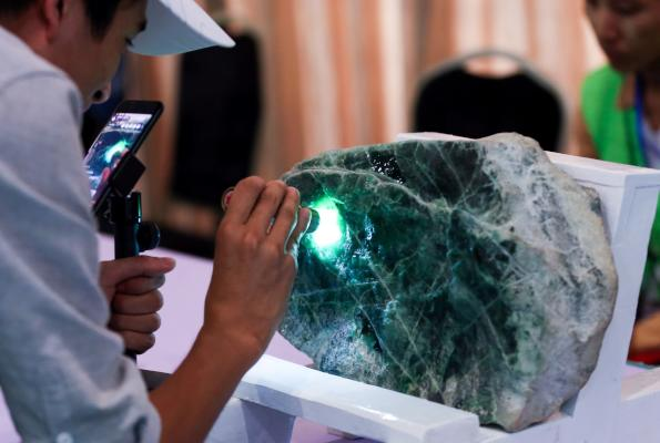 A buyer checks a jade stone before the auction during the annual Myanmar Jade, Gems and Pearl Emporium in Myanmar's capital of Naypyidaw on September 16, 2019. (AFP)