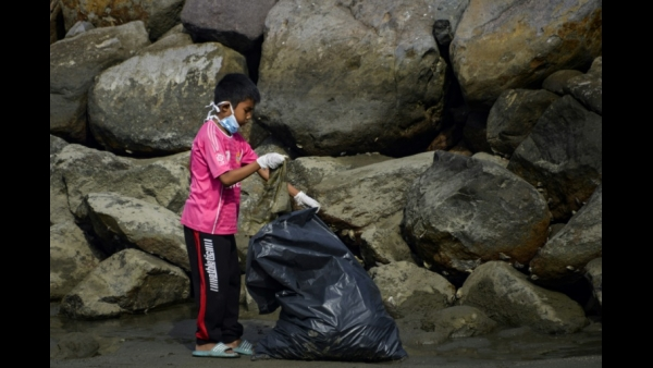 A volunteer collects trash in a coastal area as part of World Cleanup Day in Banda Aceh, Indonesia  AFP / CHAIDEER MAHYUDDIN