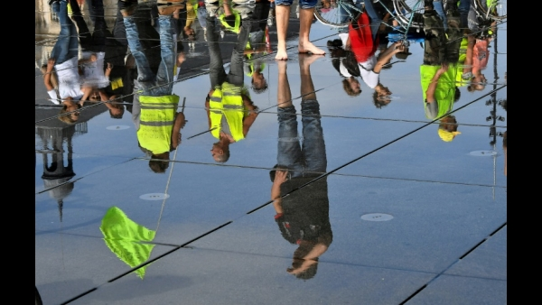 Protestors are reflected in water on the pavement as they march during a climate change and