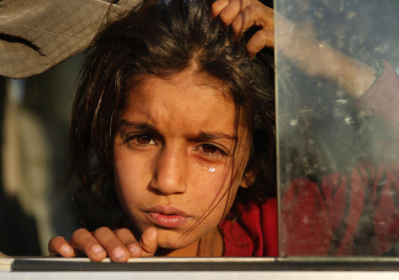 A Syrian girl who is newly displaced by the Turkish military operation in northeastern Syria, weeps as she sits in a bus upon her arrival at the Bardarash camp, north of Mosul, Iraq, Wednesday, Oct. 16, 2019. (AP Photo/Hussein Malla)
