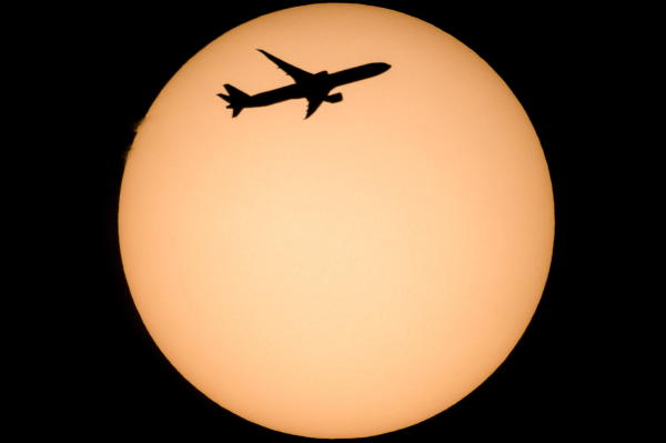 A Boeing 777-3FX type passanger plane of Etihad Airways passes in front of the Sun as photographed from Salgotarjan, northern Hungary, 20 October 2019. EPA/PETER KOMKA HUNGARY OUT