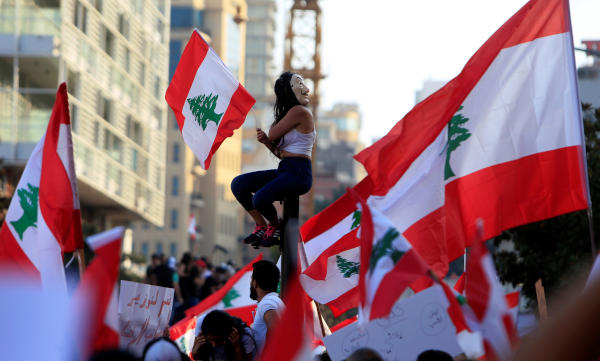A demonstrator sits on a pole while carrying a national flag during an anti-government protest in downtown Beirut, Lebanon October 20, 2019. REUTERS/Ali Hashisho