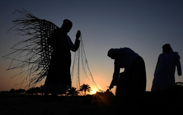 Emirati men set up fishing nets on the shore during the Dalma festival in the United Arab Emirates' island of Dalma, about 40 kilometres off of the Emirati capital Abu Dhabi on October 21, 2019. (Photo by KARIM SAHIB / AFP)