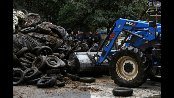 Policemen stand near tires piled by protesting farmers in Lyon, France  AFP / JEAN-PHILIPPE KSIAZEK