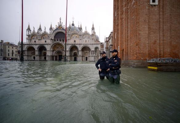 Officers from the Italian National Police stand in the flooded St. Mark's Square, by St. Mark's Basilica (L) and the Bell Tower on November 15, 2019 in Venice, two days after the city suffered its highest tide in 50 years. AFP