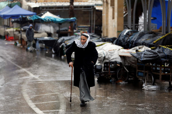 A Palestinian man walks on a street on a rainy day during a general strike over a US decision on Jewish settlements, in Hebron in the Israeli-occupied West Bank December 9, 2019. (Reuters)
