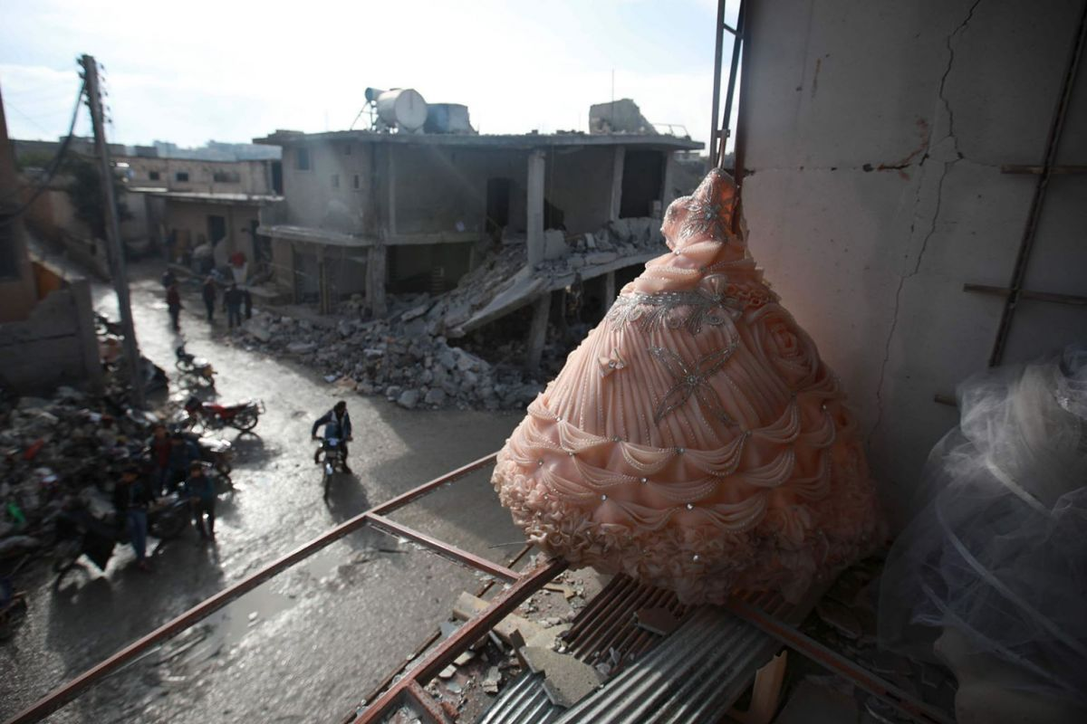 A wedding dress is seen in the destroyed window of a bridal shop in a damaged building in Balyun in Syria's northwestern Idlib province, on December 8, 2019, the day after a Russian airstrike. (AFP)