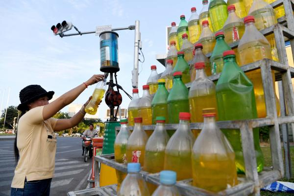 A woman fills up empty soft drink bottles with gasoline to sell along a street in Phnom Penh on December 15, 2019. (AFP)