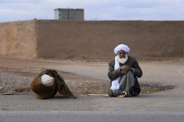 In this photo taken on January 20, 2020 a man sits next to his belongings as he waits for a taxi along a roadside on the outskirts of Herat. (AFP)