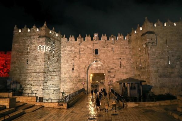People walk towards the Damascus Gate passageway to enter Old Jerusalem at night on January 20, 2020. (AFP)