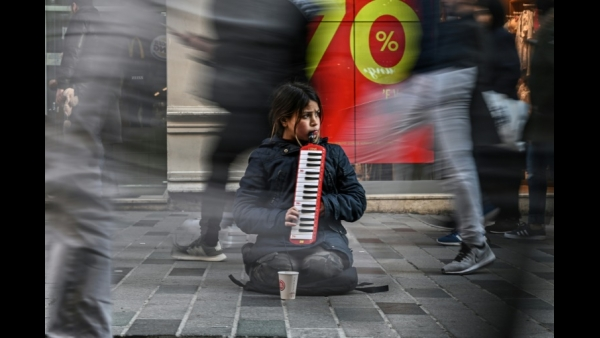 A girl plays a melodica as people walk on Istiklal avenue at Beyoglu district in Istanbul.  AFP / Ozan KOSE