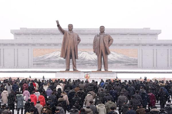 This February 16, 2020 photo shows people standing in front of statues of late North Korean leaders Kim Il Sung and Kim Jong Il in Pyongyang to celebrate the 78th anniversary of Kim Jong Il. (AFP & KCNA via KNS)