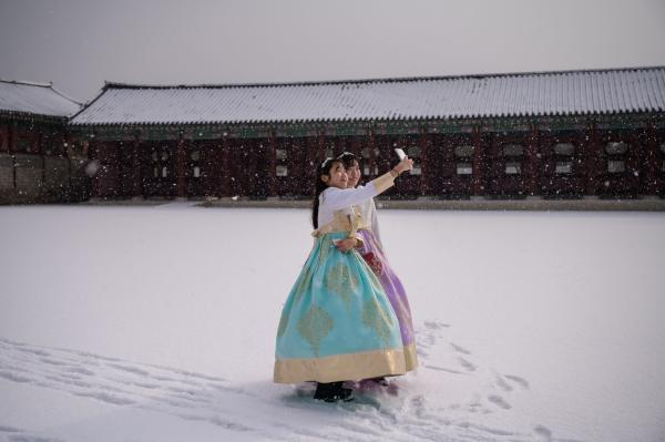 Visitors wearing traditional hanbok dress pose for selfie photos in the snow at Gyeongbokgung palace in Seoul on February 17, 2020. (AFP)