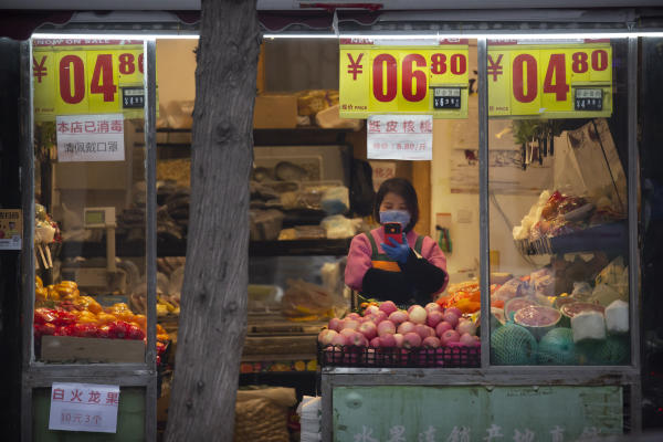 A clerk wearing a face mask looks at her smartphone as she waits for customers at a fruit shop in Beijing, Saturday, Feb. 29, 2020. (AP)