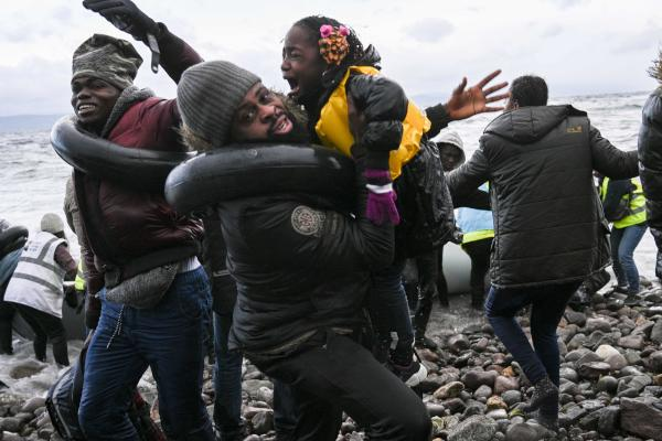 A man holds a girl as refugees from Gambia and the Republic of Congo land in Lesbos after being rescued by a war ship while crossing the sea between Turkey and Greece on February 29, 2020. (AFP)
