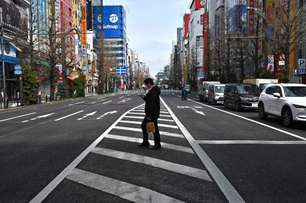 A man wearing a face mask, amid concerns of the COVID-19 coronavirus, crosses a street in the Akihabara district in Tokyo on March 30, 2020. (AFP)