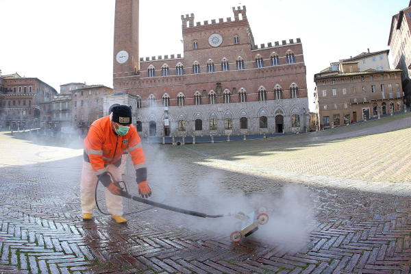 Sanitation workers wearing protective clothing and face masks carry out the cleaning of Piazza del Campo Square in Siena, Italy, 01 April 2020. EPA/FABIO DI PIETRO
