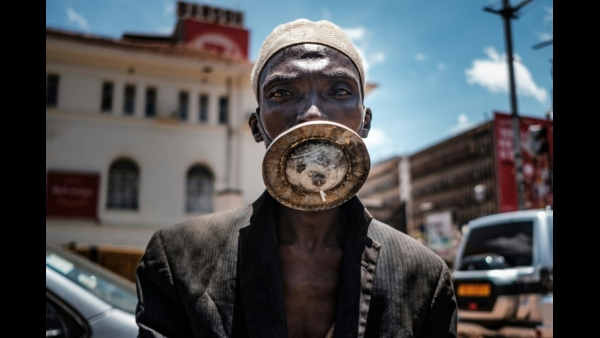 A man wearing an alternative mask poses for a photograph in Kampala, Uganda.  AFP / SUMY SADURNI