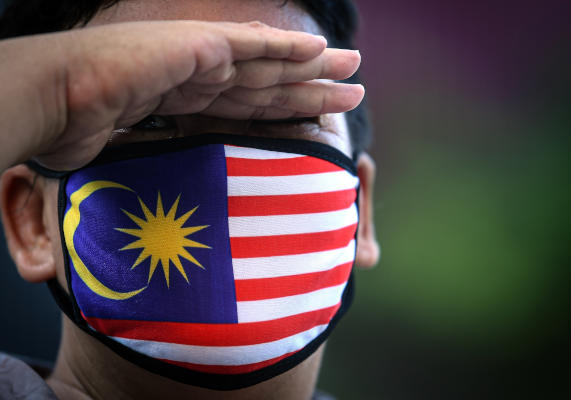 04 April 2020, Malaysia, Kuala Lumpur: A person wearing a face mask bearing the colors of the Malaysian flag waits for a bus at a bus stop. Photo: Iskandar/BERNAMA/dpa