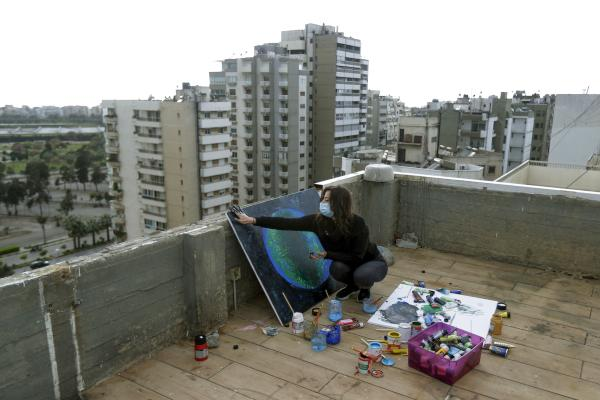 Lebanese Artist Hayat Nazer draws a painting on the roof of her family's apartment building in the northern coastal city of Tripoli, where she stays confined with her family due to the coronavirus pandemic, on April 8, 2020. (Photo by Joseph EID / AFP)