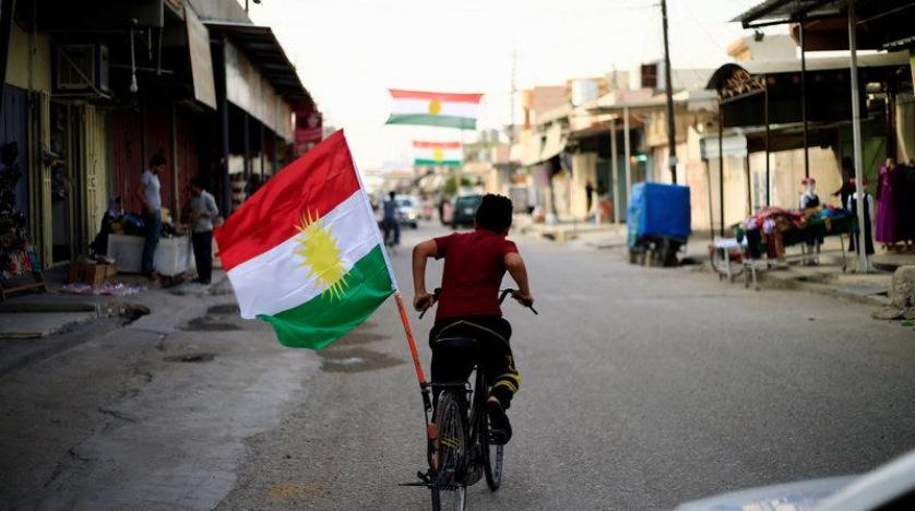 A boy rides a bicycle with the flag of Kurdistan in Tuz Khurmato Iraq