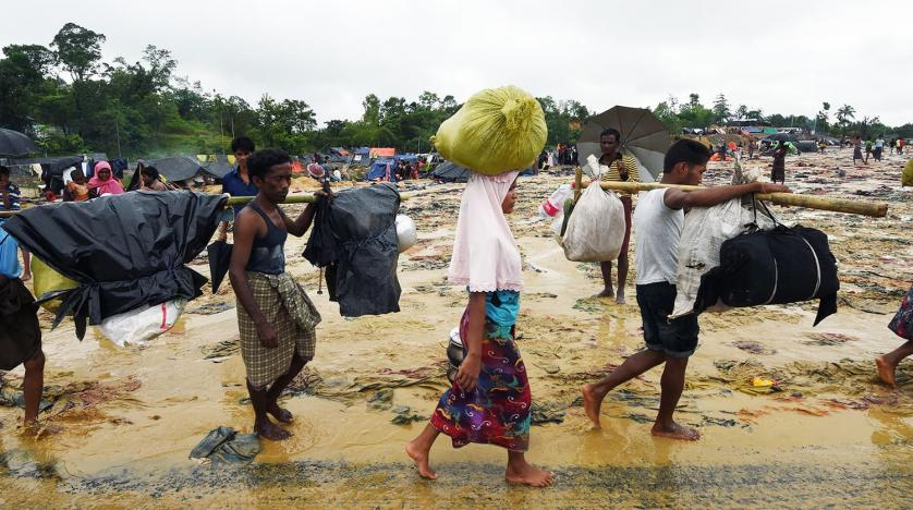Rohingya refugees walk in the rain in Bangladesh's Balukhali refugee camp. AFP file
