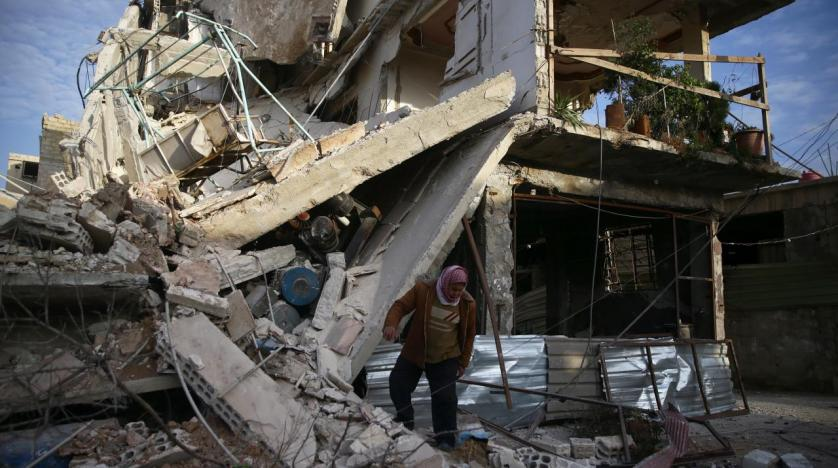 A person inspects damaged building in the besieged town of Douma Eastern Ghouta Damascus Syria