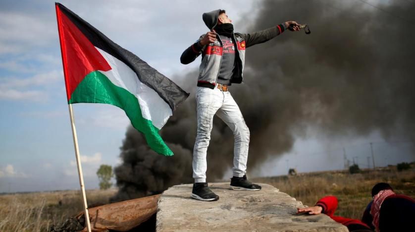 A Palestinian demonstrator uses a slingshot to hurl stones towards Israeli troops during clashes at a protest near the Gaza Israel border