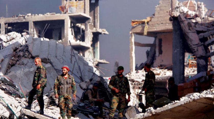 Syrian forces stand on the rubble of damage buildings in al Hajar al-Aswad Syria