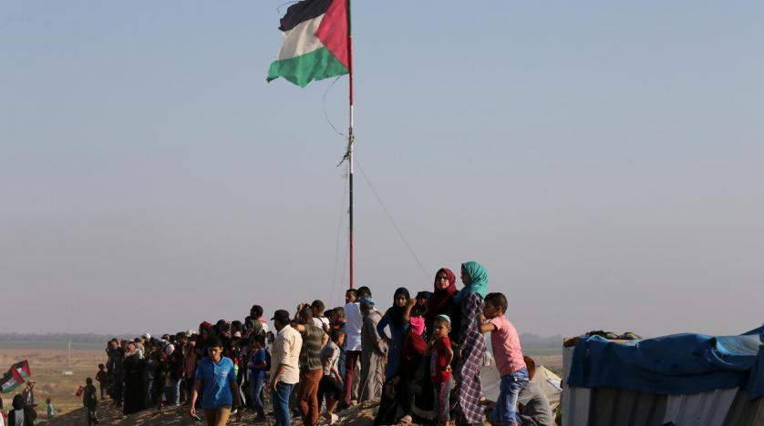 Palestinians watch a protest at the Israel Gaza border in the southern Gaza Strip