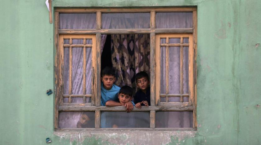 Afghan children look out from a broken window at the site of a blast in Kabul Afghanistan